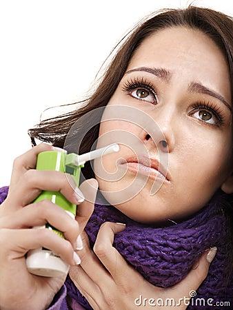 Woman using throat spray.