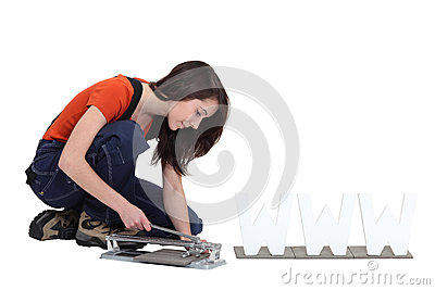 Woman using a tile cutter