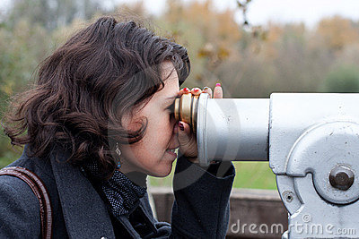 Woman using a touristic telescope