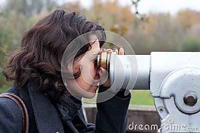 Woman using a touristic telescope