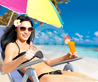 Woman on vacation at beach with thumbs up sign