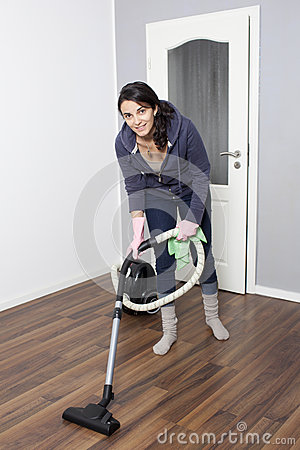 Woman vacuums the flat