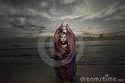 Woman with a veil on the beach