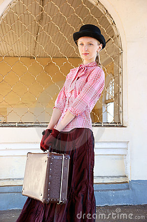Woman in vintage dress with suitcase