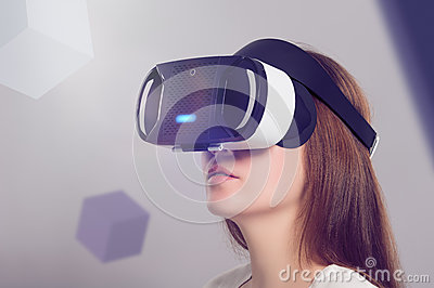Woman in VR headset looking up at the objects in virtual reality Stock Photo