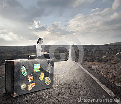 Woman waiting on a bench with a suitcase