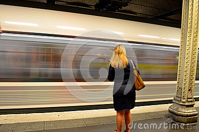 Woman waiting in front of moving subway train