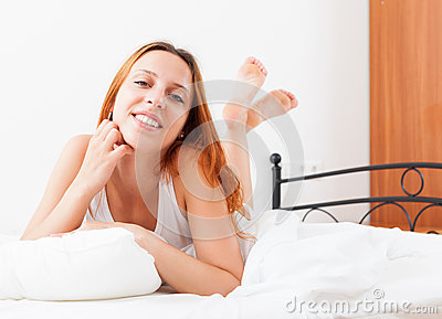 Woman waking up in her bed at home