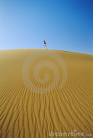 Woman walking across desert sand dune