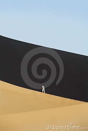Woman walking across desert sand dunes