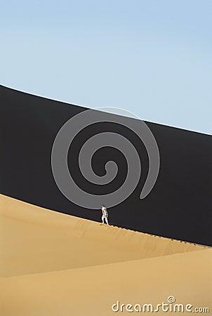 Woman walking across desert sand dunes