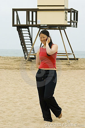 Woman walking away from life guard tower, smiling