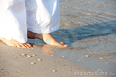 Woman walking barefoot on the beach