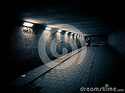 Woman walking in a dark tunnel