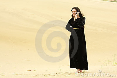 Woman walking by desert calling on cellphone