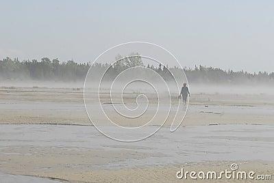 Woman walking on a foggy beach