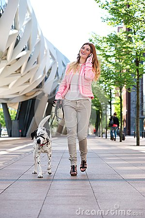 Woman walking her dog and talking on cellphone in the city