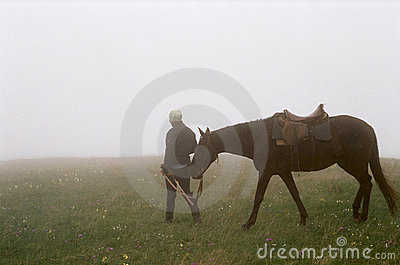 Woman walking horse in fog