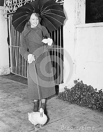 Free Woman Walking In The Rain With A Duck On A Leash Royalty Free Stock Photo - 52030275