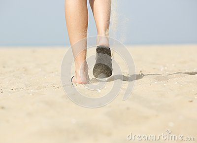Woman walking on sand at beach in slippers