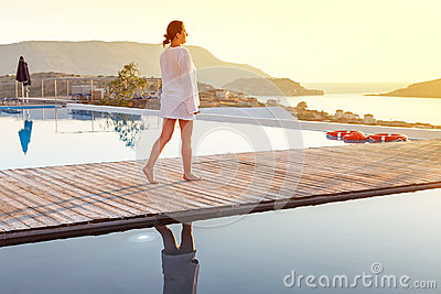Woman walking at sunrise near swimming pool