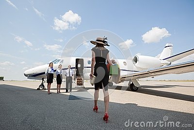 Woman Walking Towards Private Jet At Airport