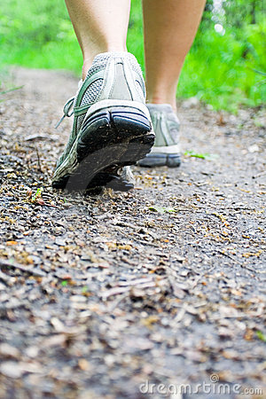 Woman walking on trail in forest, sport shoes