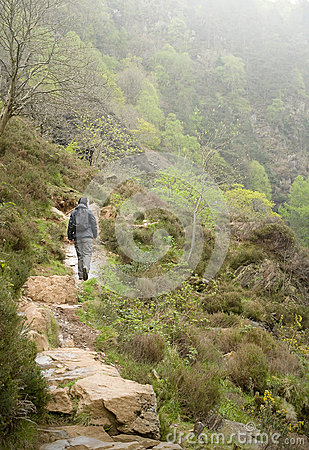Woman walking up a mountain on stone path