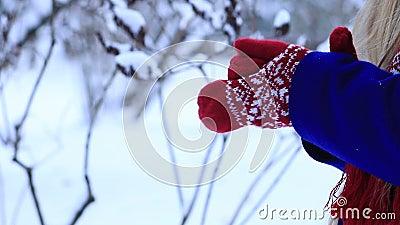 Woman warming frozen hands in mittens stock footage