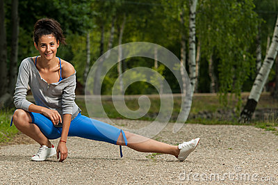 Woman warms her leg muscles before jogging