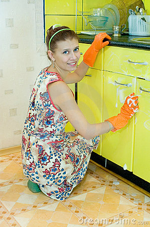 The woman washes kitchen furniture