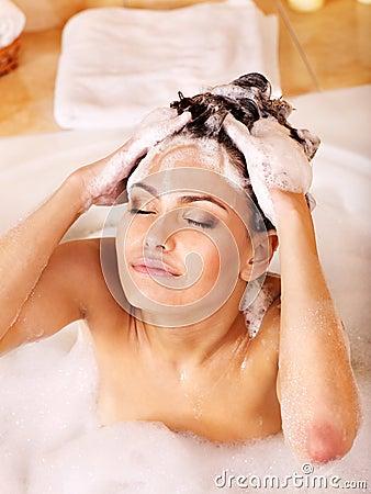 Woman washing hair by shampoo .