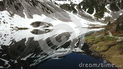 Woman watching glacier with reflections in the lake. This is an aerial footage of a woman watching glacier with reflections in the lake stock video footage