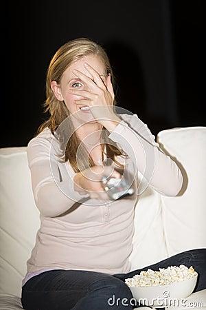 Woman Watching Horror Movie On Sofa