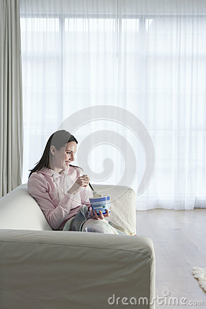 Woman Watching TV While Eating Icecream