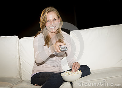 Woman Watching TV While Having Popcorn On Sofa