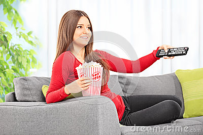 Woman watching tv seated on sofa at home