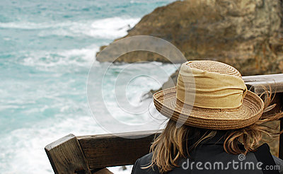A Woman Watching Waves Crash over rocks on Beach