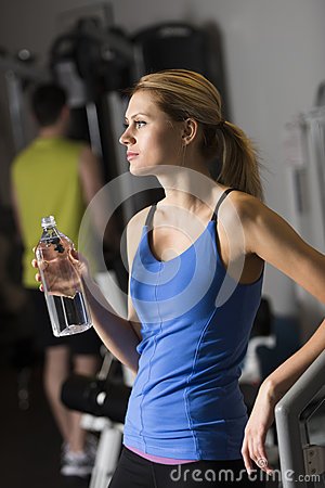 Woman With Water Bottle Looking Away At Gym