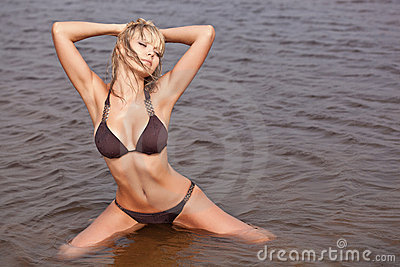 Woman in water wearing brown bikini