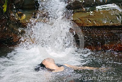 Woman in waterfall