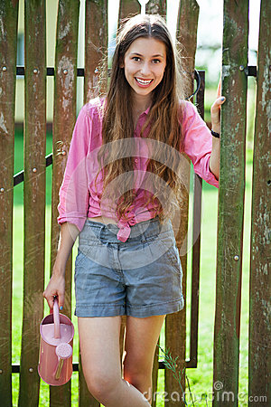 Woman with watering can by wooden fence