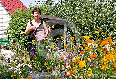 Woman waters flowers on summer residence