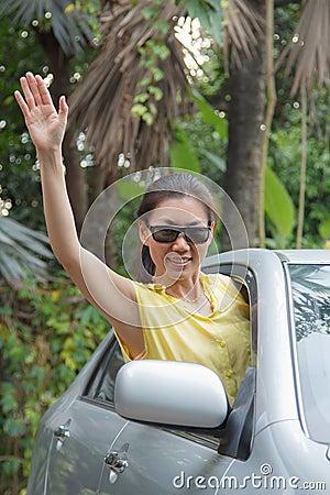 Woman waving in the car