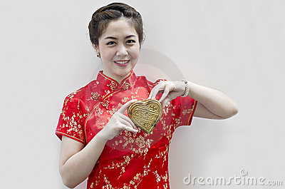 Woman wear cheongsam and holding golden heart