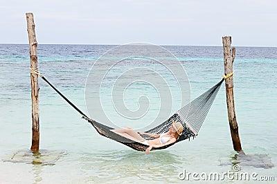 Woman Wearing Bikini And Sun Hat Relaxing In Beach Hammock