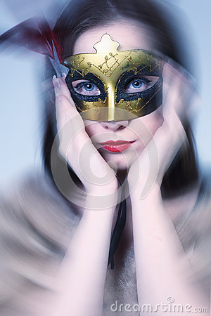 Woman  wearing  carnival venetian mask on blur background.