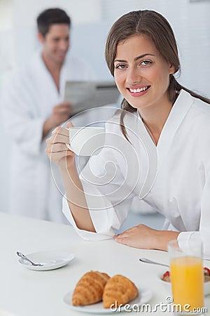 Woman wearing a dressing gown having breakfast