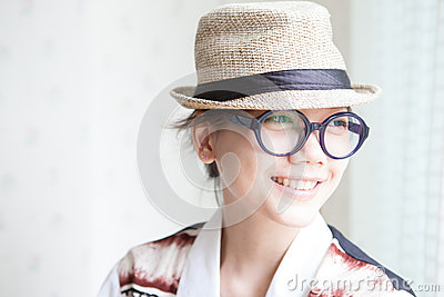 Woman wearing a glasses and straw hat smilling