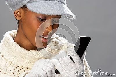 Woman Wearing Knitwear In Studio Using Mobile